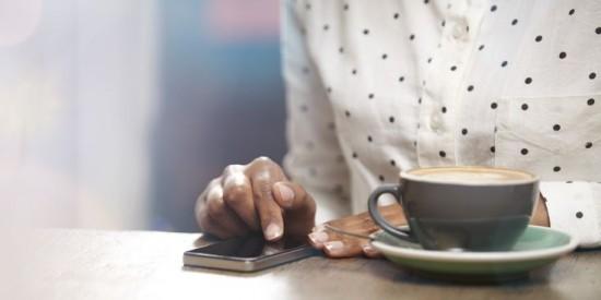 persona usando smartphone su tavolo con tazza