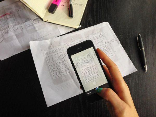 mano fotografando foglio con smartphone
