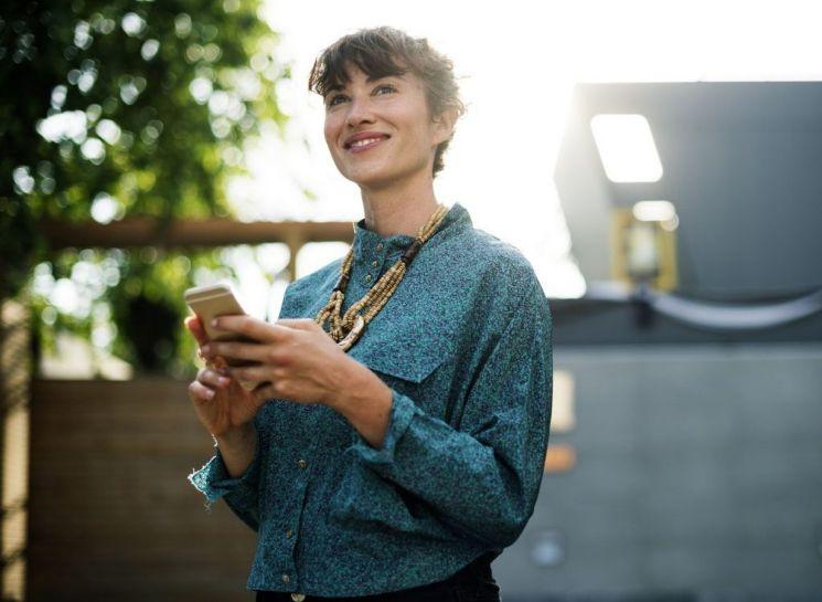 Rgazza felice con smartphone in mano
