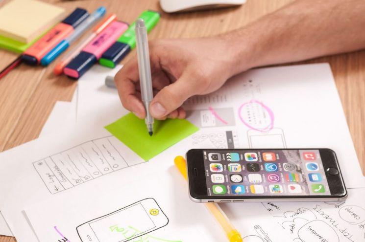 persona disegnando su fogli con smartphone