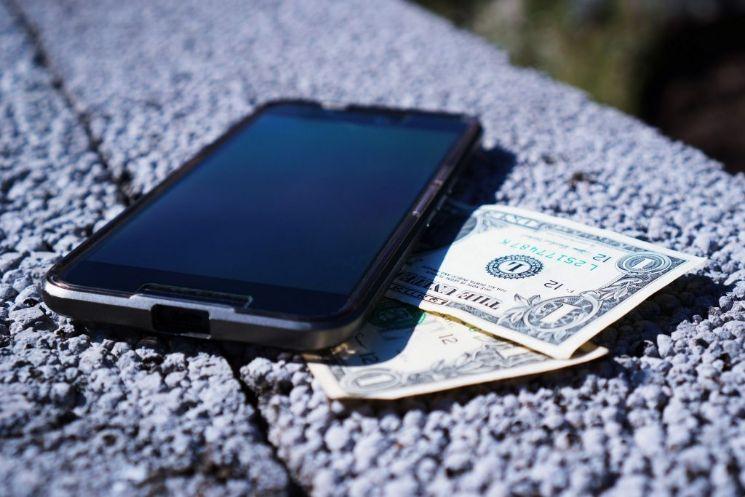 Smartphone e banconote dollari - quanto costa creare un app