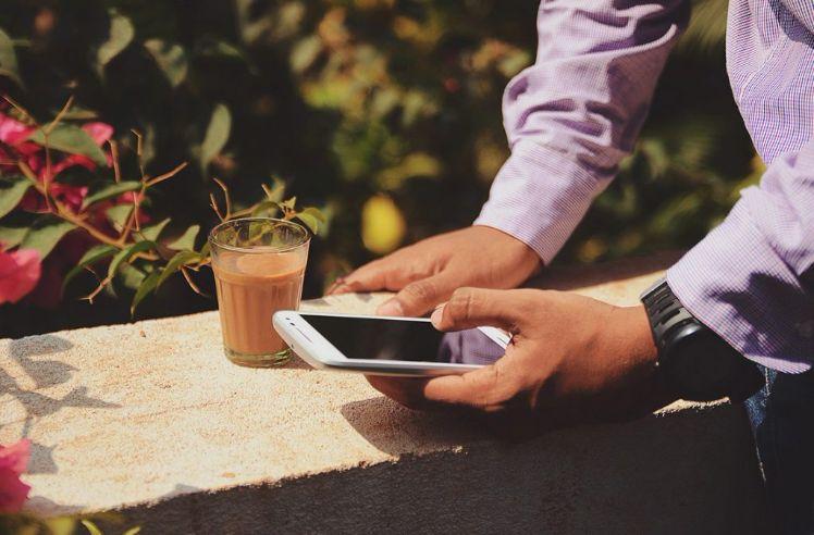 persona con smartphone e bicchiere