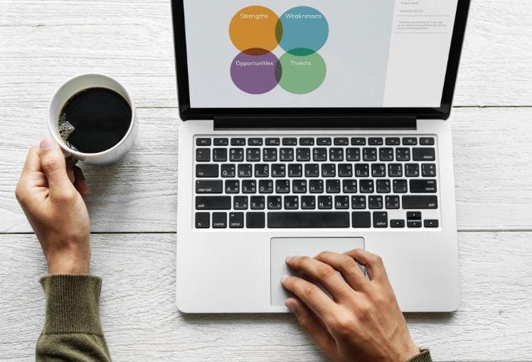 mani con laptop e tazza di caffè
