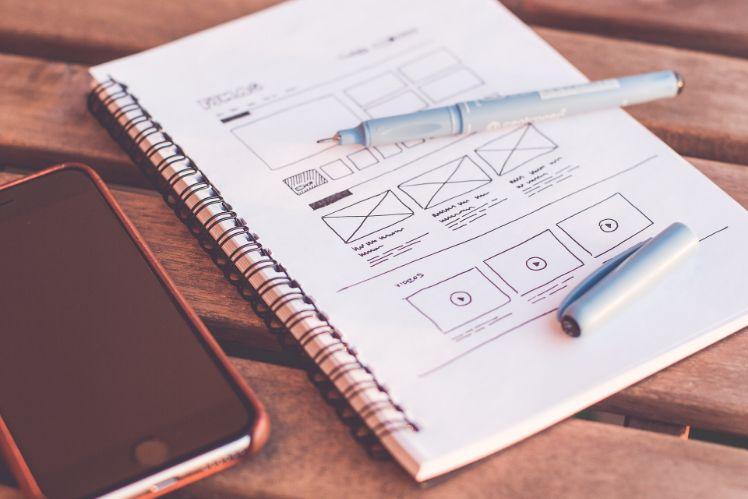 quaderno con scritte e smartphone su tavolo