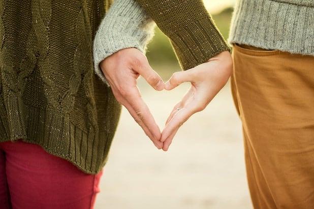 uomo e donna che si tengono per mano - entrambe le mani formano un cuore a forma di cuore insieme