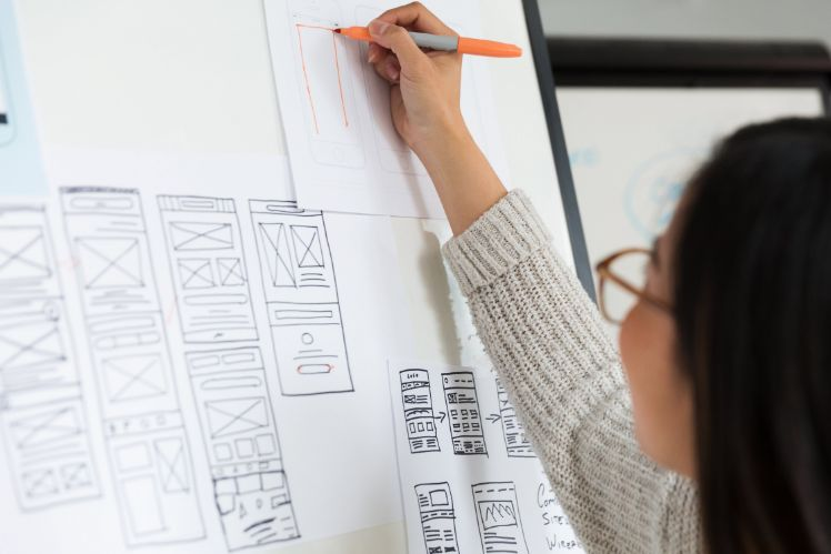 persona che disegna wireframes su una lavagna