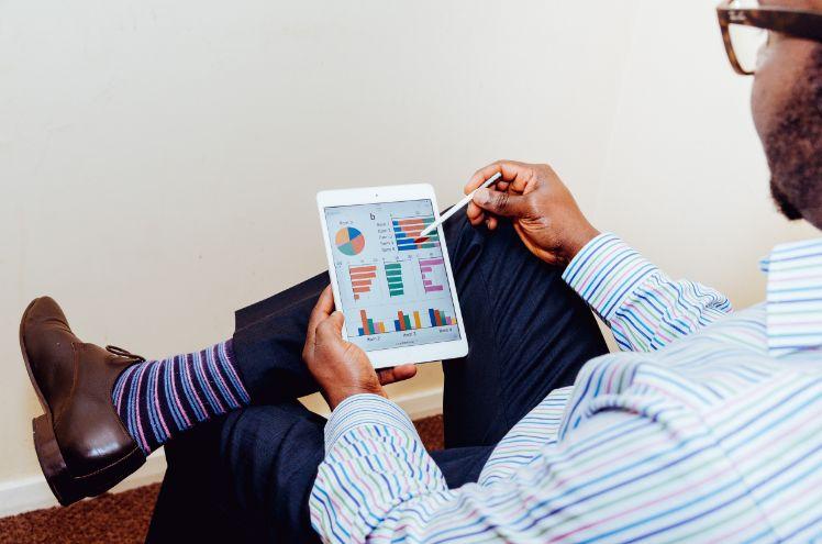 uomo seduto guardando analisi su iPad