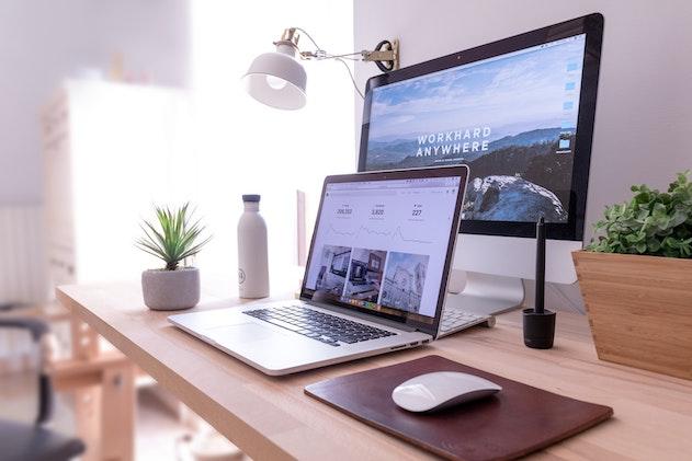 scrivania con computer fisso e laptop