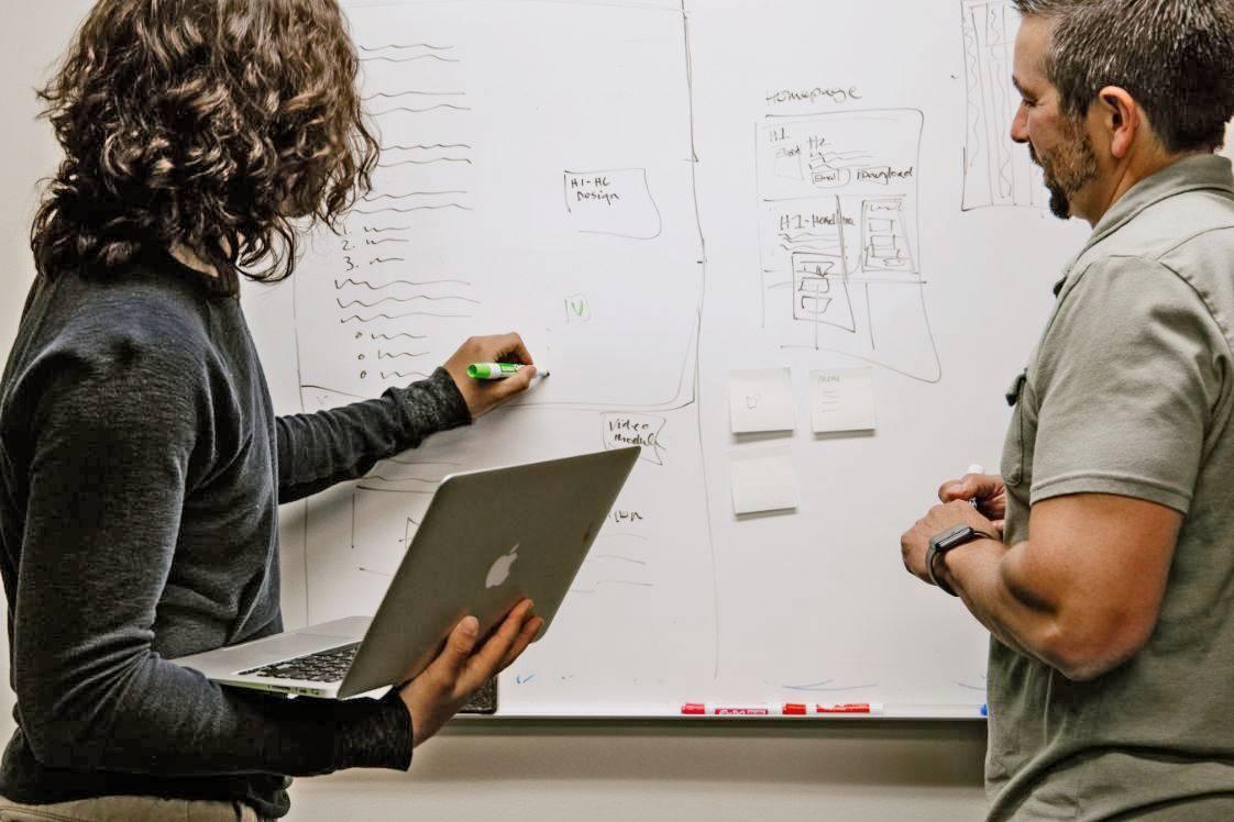 due persone scrivendo su una lavagna
